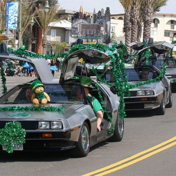 A group of DeLorean cars and their iconic gull-wing doors cruise down Pier Avenue during 20th Hermosa Beach St. Patrick's Day Parade (Photo by South Bay Events).